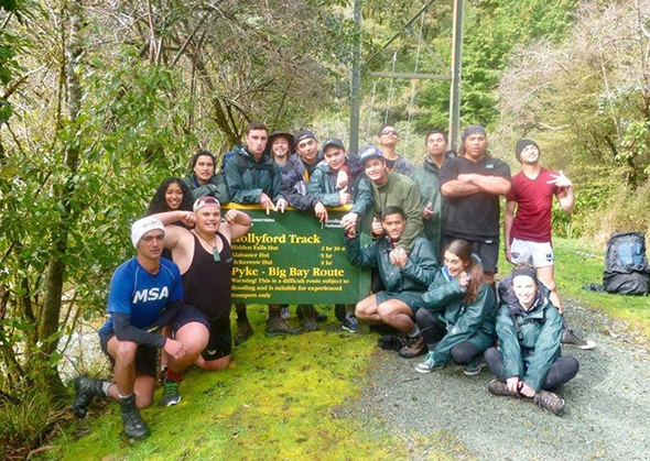 Rakatahi in front of the Hollyford Track sign.